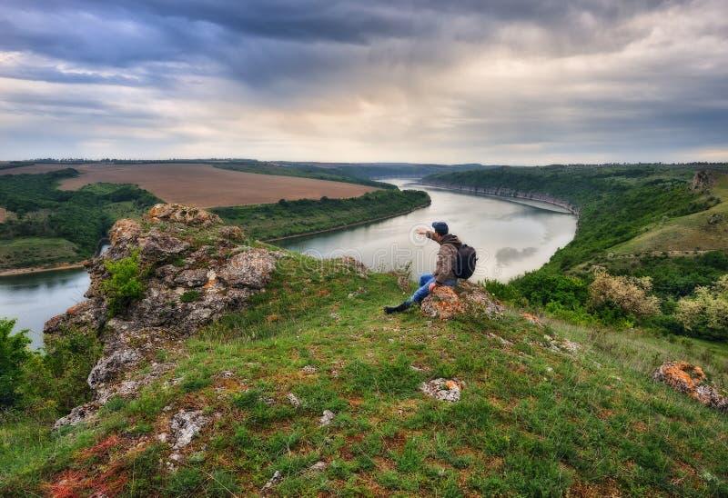 Uomo su una roccia sopra un fiume fotografia stock
