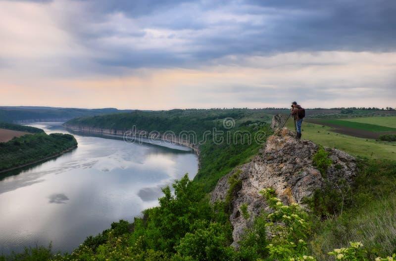 Uomo su una roccia sopra un fiume immagini stock libere da diritti