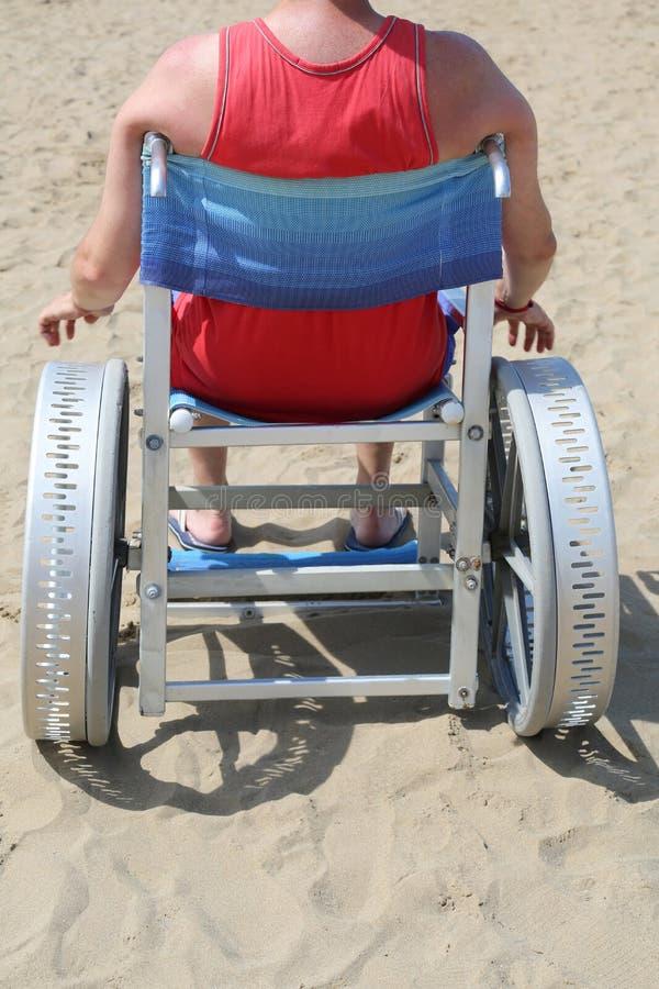 Uomo su uno speciale della sedia a rotelle per la spiaggia fotografia stock