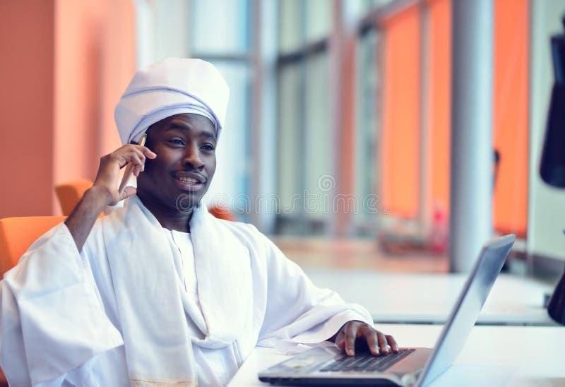 Uomo sudanese di affari in attrezzatura tradizionale facendo uso del telefono cellulare in ufficio fotografia stock