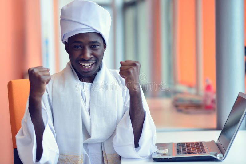 Uomo sudanese di affari in attrezzatura tradizionale facendo uso del telefono cellulare in ufficio immagini stock libere da diritti