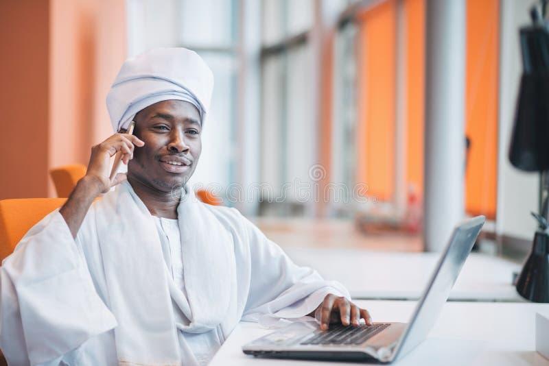 Uomo sudanese di affari in attrezzatura tradizionale facendo uso del telefono cellulare in ufficio fotografia stock libera da diritti