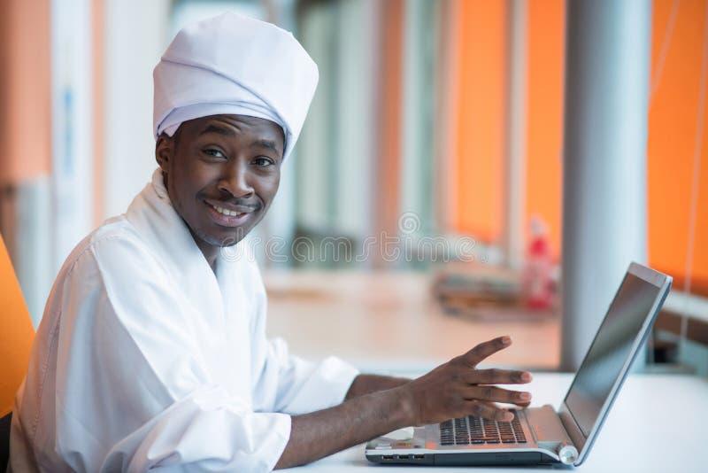 Uomo sudanese di affari in attrezzatura tradizionale facendo uso del telefono cellulare in ufficio fotografie stock libere da diritti