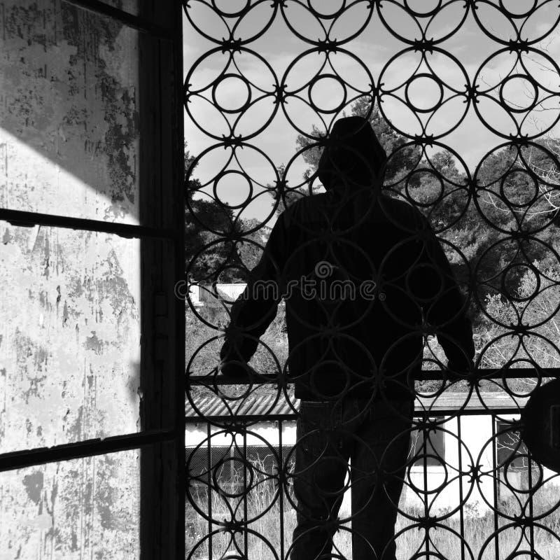 Uomo sul balcone della casa abbandonata fotografie stock