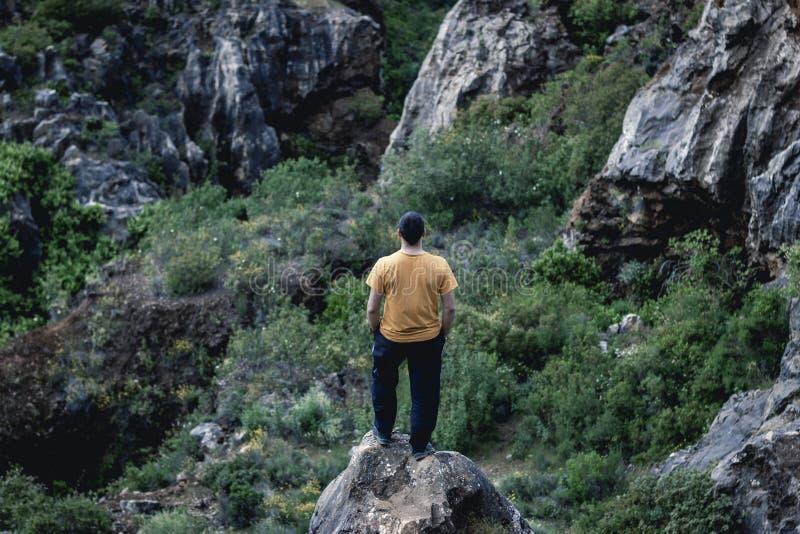Uomo sul bordo della scogliera sulla natura fotografia stock
