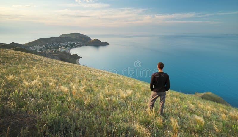 Uomo sul bordo Scogliera della montagna e del mare fotografie stock libere da diritti