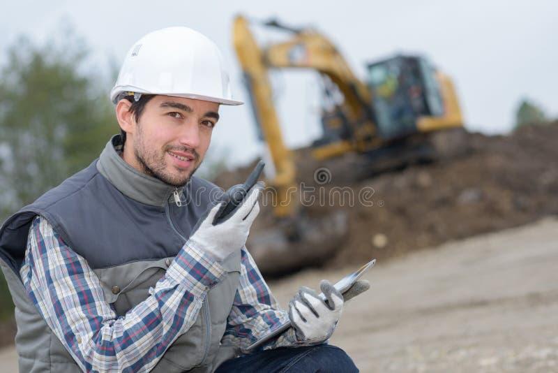 Uomo sul cantiere che convince walkie-talkie fotografia stock