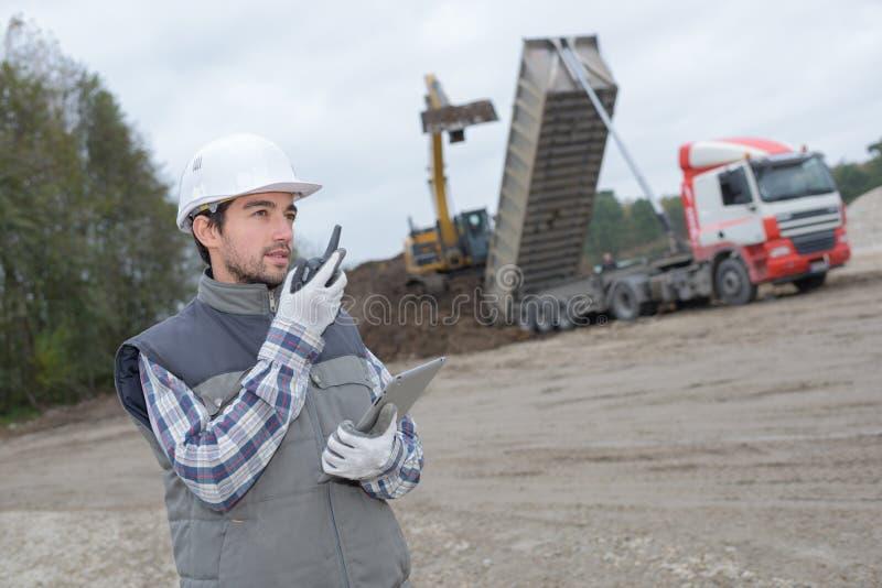 Uomo sul cantiere che convince walkie-talkie fotografie stock