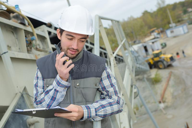 Uomo sul cantiere che convince walkie-talkie fotografia stock libera da diritti