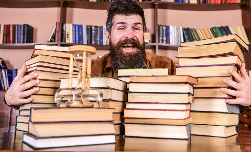 Uomo sul fronte felice fra i mucchi dei libri, mentre studiando nella biblioteca, scaffali per libri su fondo Concetto del biblio fotografia stock