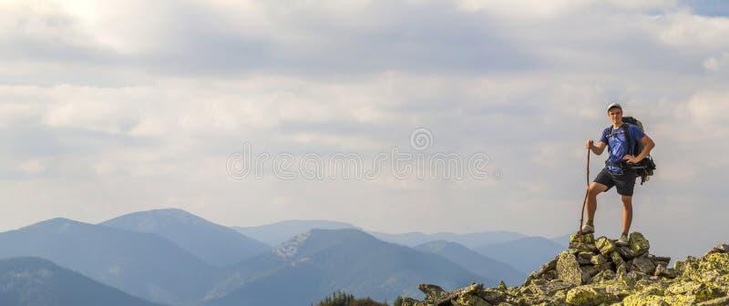 Uomo sul picco della montagna Scena impressionabile Giovane con backpac fotografie stock libere da diritti
