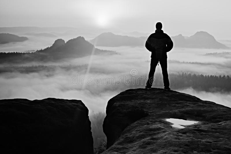 Uomo sul picco della roccia dell'arenaria in parco nazionale Sassonia Svizzera che guarda per esporre al sole Bello momento fotografia stock libera da diritti