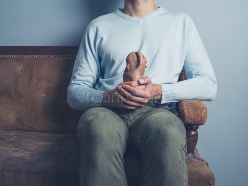 Uomo sul sofà con la patata sconosciuta immagine stock