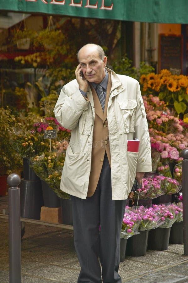 Uomo sul telefono cellulare davanti al fiorista, Parigi, Francia immagine stock