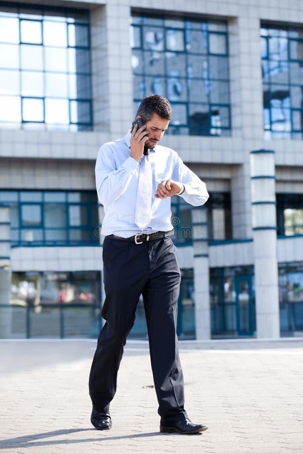 Uomo sul telefono e sul controllo della sua vigilanza immagine stock libera da diritti