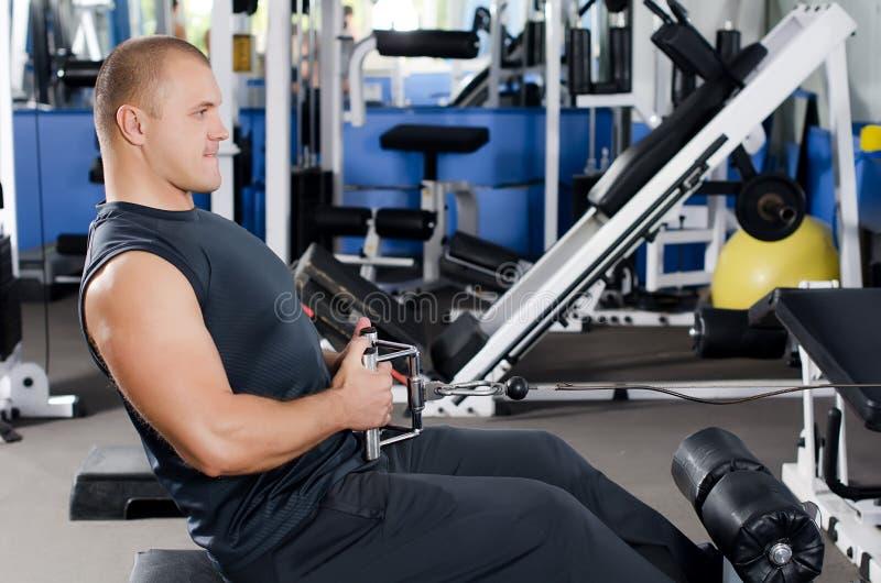 Uomo sull'apparecchiatura di addestramento in randello fotografie stock libere da diritti