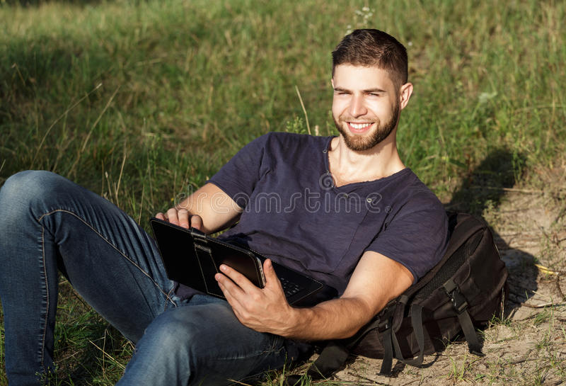 Uomo sull'aumento in natura facendo uso della compressa digitale fotografia stock libera da diritti