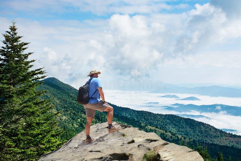 Uomo sull'escursione del viaggio, stante sopra la montagna sopra le nuvole, godenti di bello paesaggio della montagna di estate immagine stock