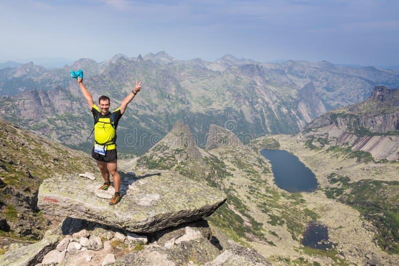 Uomo sulla cima della collina che guarda paesaggio meraviglioso in montagne durante l'estate fotografia stock libera da diritti