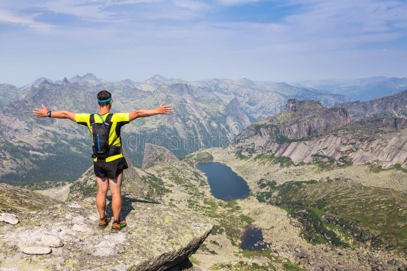 Uomo sulla cima della collina che guarda paesaggio meraviglioso in montagne durante l'estate immagini stock