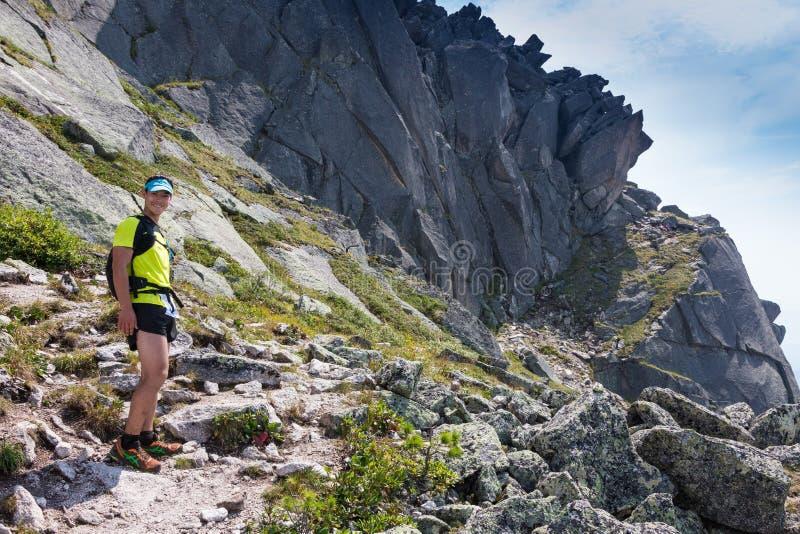 Uomo sulla cima della collina che guarda paesaggio meraviglioso in montagne durante l'estate immagine stock