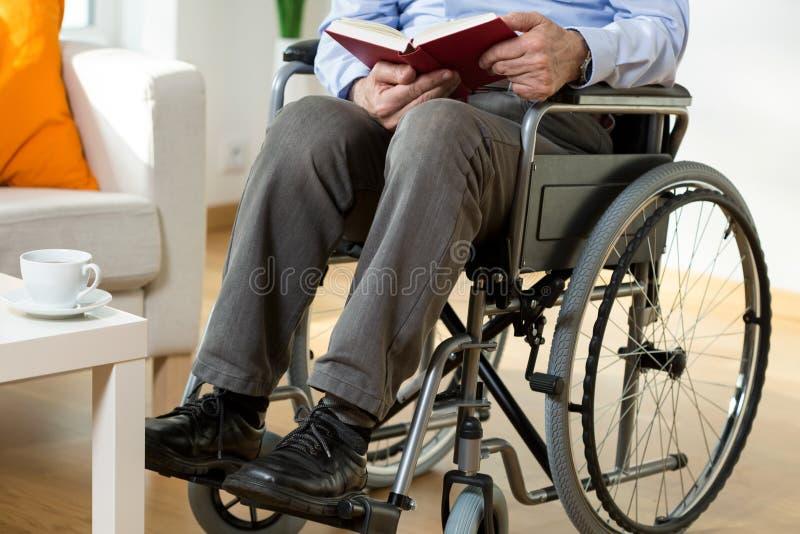 Uomo sulla sedia a rotelle che legge un libro immagine stock libera da diritti