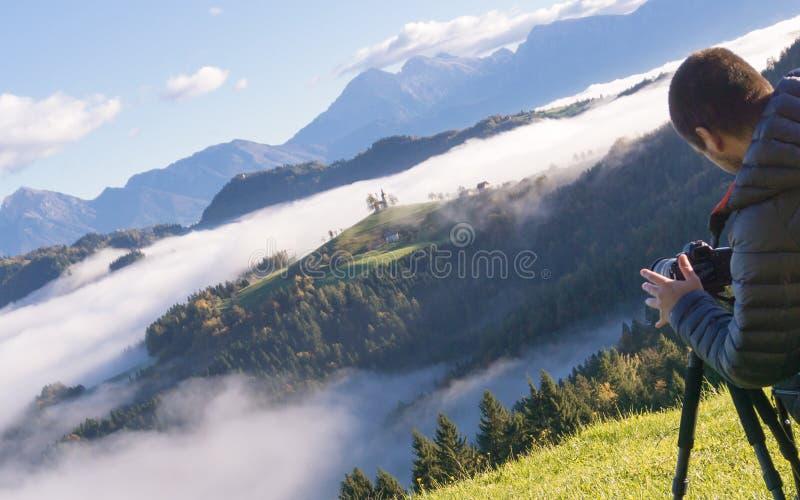 Uomo sulla sedia a rotelle che prende le foto di bello paesaggio in una mattina nebbiosa, st Thomas Slovenia immagini stock libere da diritti