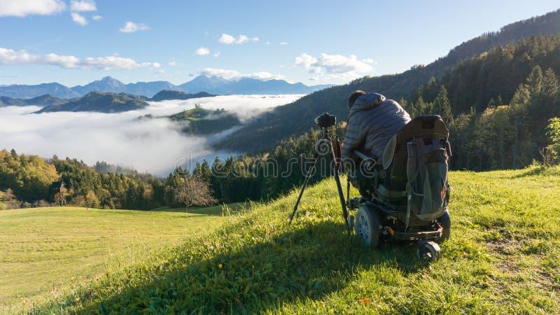 Uomo sulla sedia a rotelle che prende le foto di bello paesaggio in una mattina nebbiosa, st Thomas Slovenia immagine stock