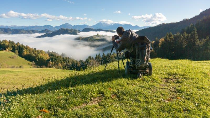 Uomo sulla sedia a rotelle che prende le foto di bello paesaggio in una mattina nebbiosa, st Thomas Slovenia fotografia stock