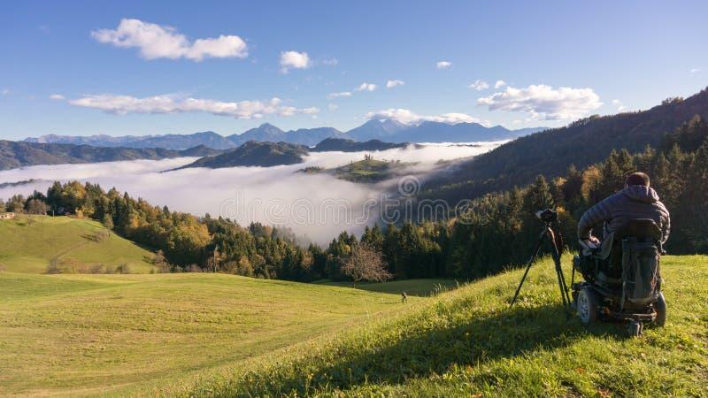Uomo sulla sedia a rotelle che prende le foto di bello paesaggio in una mattina nebbiosa, st Thomas Slovenia fotografia stock libera da diritti