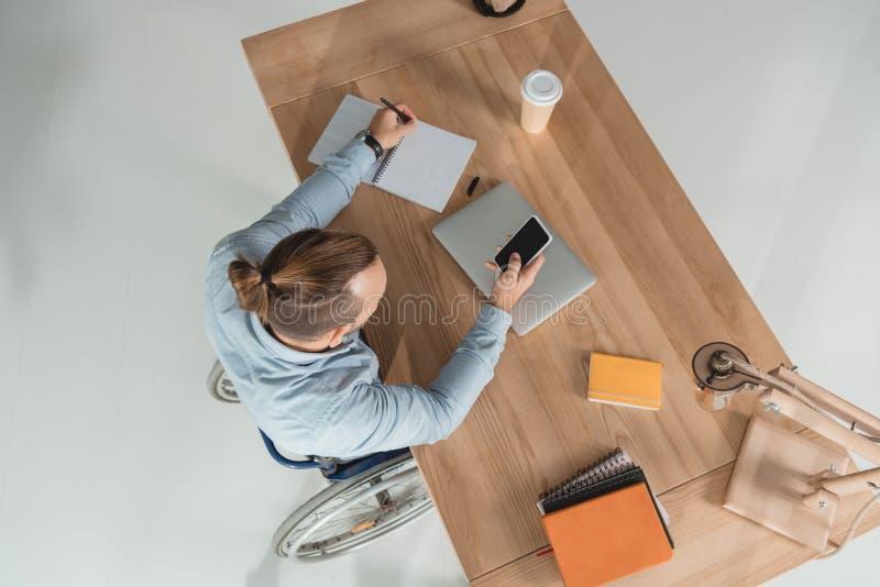 Uomo sulla sedia a rotelle facendo uso dello smartphone immagini stock libere da diritti