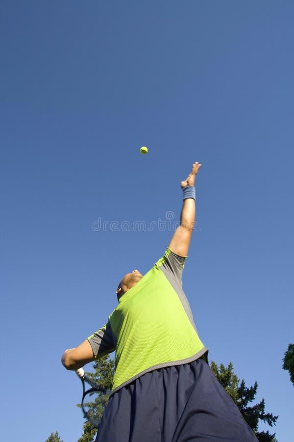 Uomo sulla sfera di tennis del servizio della corte di tennis - verticale fotografie stock