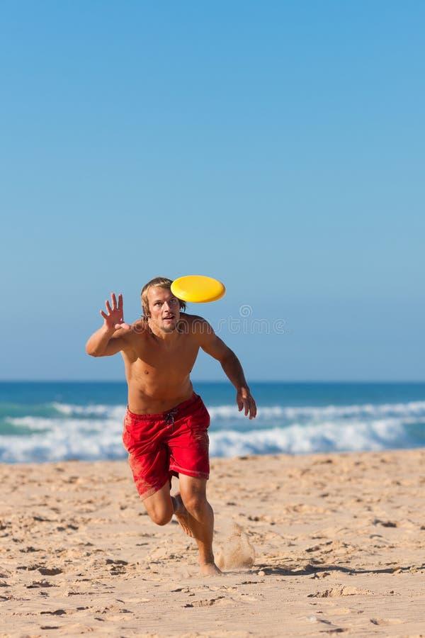 Uomo sulla spiaggia che gioca Frisbee fotografie stock