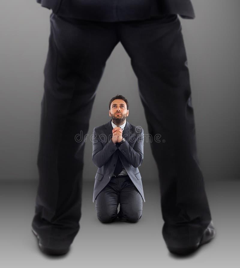 Uomo sulle sue ginocchia che prega per non essere allontanato fotografia stock