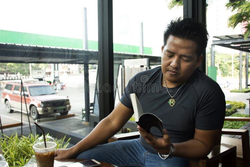 Uomo tailandese che si siede parlare ed il libro di lettura rilassato con il caffè di ghiaccio bevente nel negozio del caffè fotografia stock libera da diritti