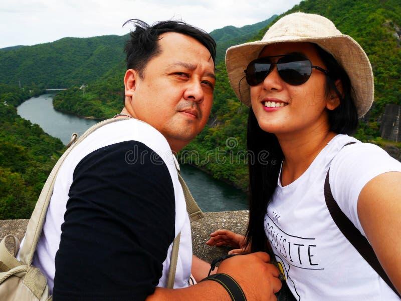 Uomo tailandese e visita dei viaggiatori degli amanti delle donne alla diga di Bhumibol a Tak, Tailandia immagini stock libere da diritti