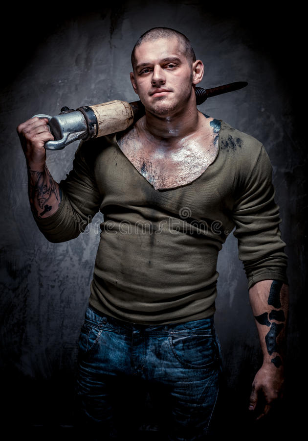 Uomo tatuaato muscolare con il jackhammer fotografia stock libera da diritti