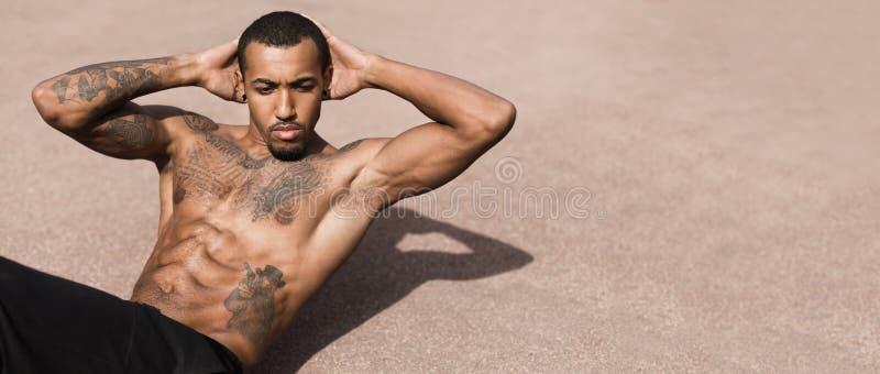 Uomo tatuato di afro che esercita Sit Ups On Sports Ground fotografia stock