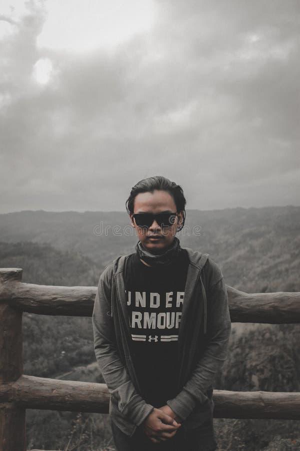 Uomo in top nero e giacca di oodie grigio in piedi accanto a legno di marrone fotografia stock