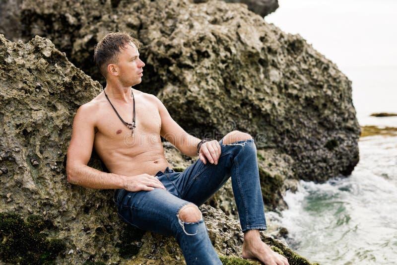 Uomo topless in jeans che si siedono sulle rocce dall'oceano fotografia stock