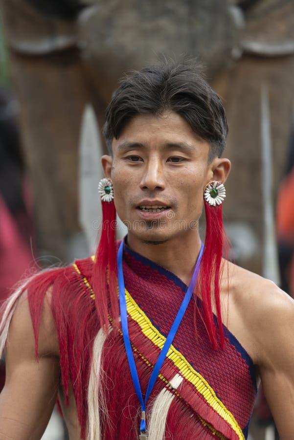 Uomo tribale del Naga con gli orecchini unici al festival del bucero, Nagaland, India il 1° dicembre 2013 immagini stock