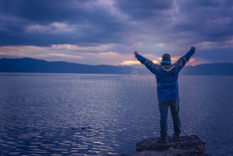 Uomo trionfante sulla riva del lago fotografia stock