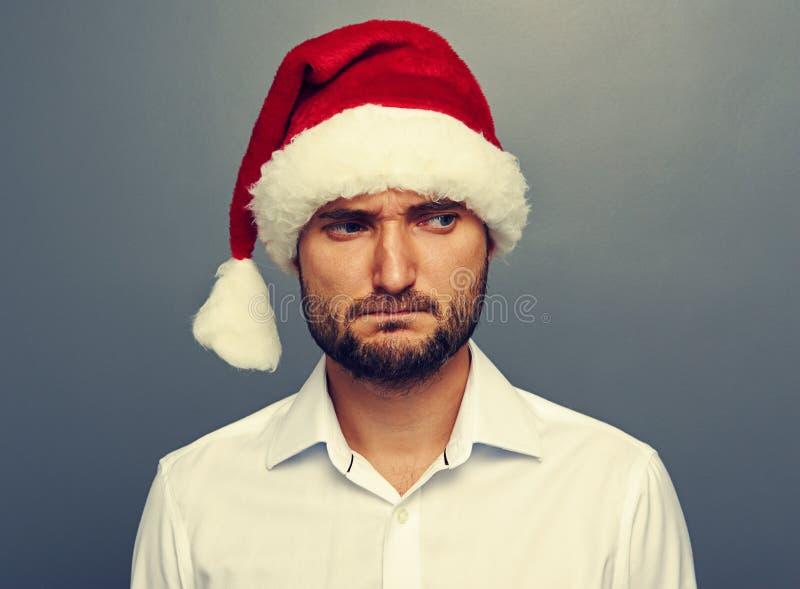 Uomo triste in cappello di Santa sopra buio fotografia stock libera da diritti