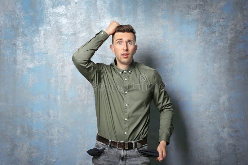 Uomo triste che mostra le sue tasche vuote fotografia stock libera da diritti