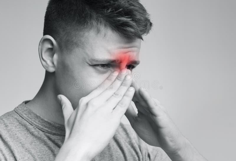 Uomo triste che tiene il suo naso perché dolore del seno immagine stock libera da diritti