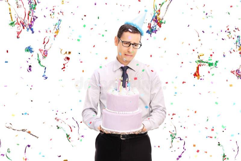 Uomo triste che tiene una torta di compleanno e gridare fotografia stock
