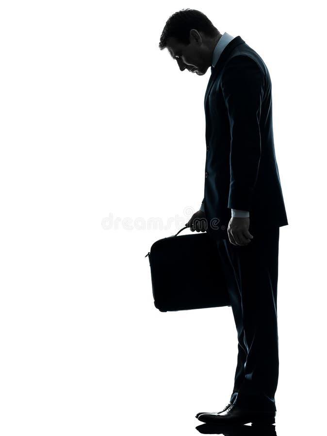 Uomo triste di affari che guarda giù la siluetta fotografie stock