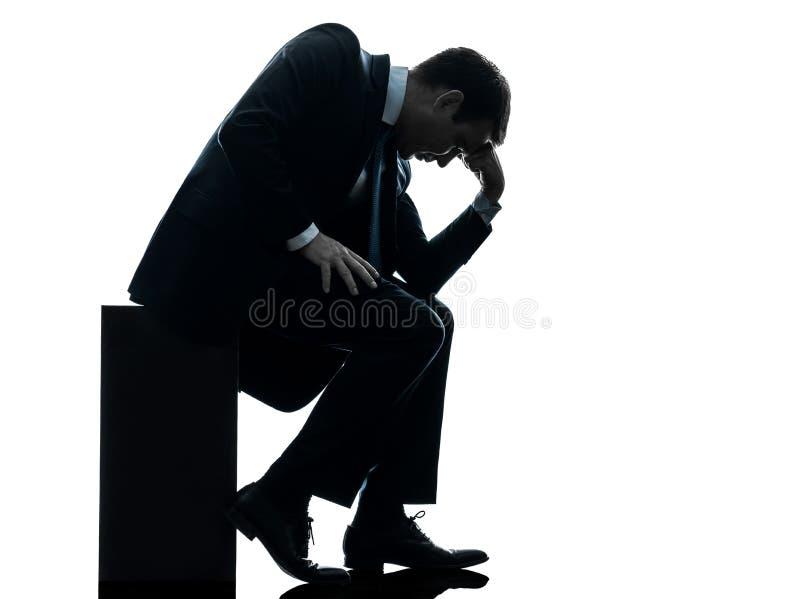 Uomo triste di affari che si siede siluetta pensierosa immagini stock libere da diritti