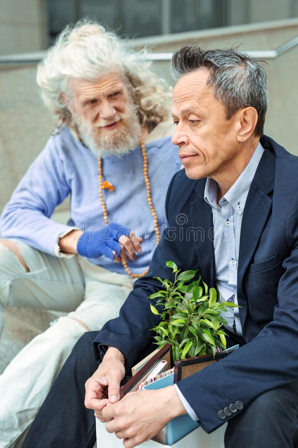 Uomo triste pessimistico che si siede vicino al hippy ispirato immagini stock libere da diritti