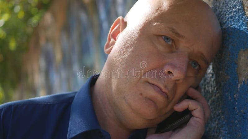 Uomo triste vicino ad una parete sulla prova della via per iniziare una telefonata fotografia stock libera da diritti